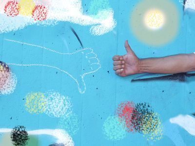 A person giving a thumbs up against a wall with a drawing of a thumbs down, representing core values.
