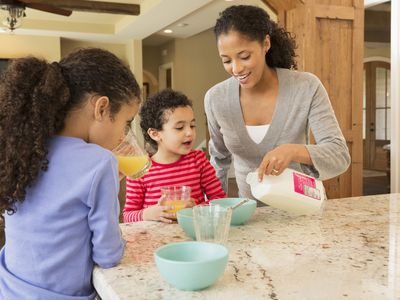 A picture of a mom pouring cereal for her children
