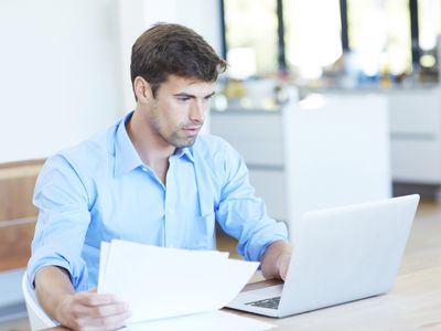 Man holding documents and working on computer