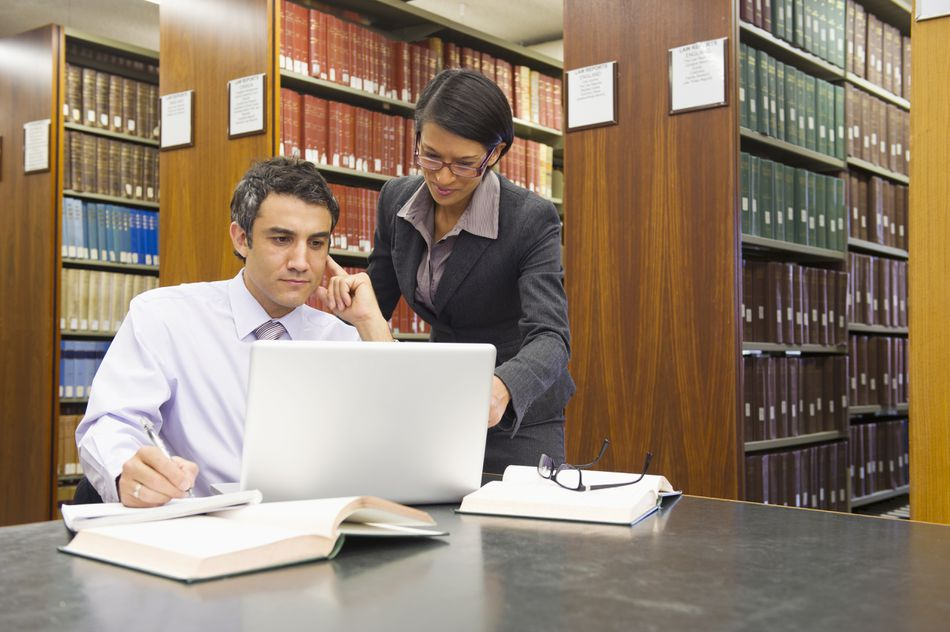 Two lawyers in a library in front of a laptop