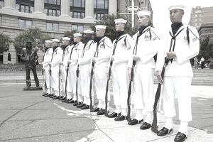 Members of the U.S. Navy Ceremonial Guard stand in formation next to the Lone Sailor statue at the U.S. Navy Memorial.