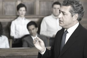 A male lawyer talking in a courtroom in front of a jury