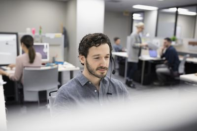Salesman talking on telephone with headset at cubicle