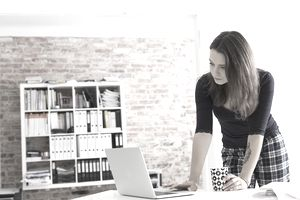 Young woman in pajamas using laptop