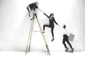 A step ladder with a person on top helping a person mid-way up climb the ladder who is helping someone on the ground.