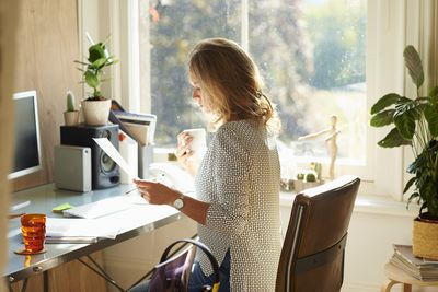 Woman drinking coffee and reading paperwork at desk in sunny home office
