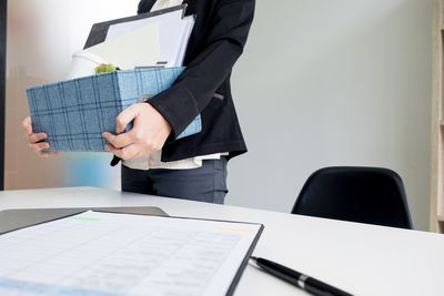 Midsection Of Woman Holding Box By Table At Office