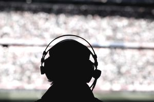Silhouette of broadcast presenter against filled stadium seating