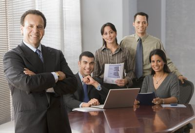 3d5fc2baaec Hispanic businesspeople dressed in a range of business formal attire  options are in a conference room