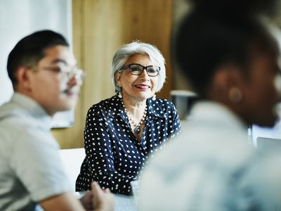 Smiling mature female business owner listening during presentation during meeting in office conference room