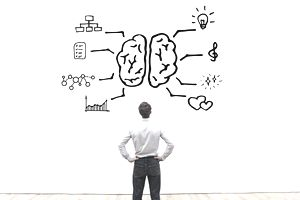 person looking at drawing of a human brain and cognitive skills symbols on a otherwise blank wall.
