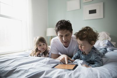 Father and children using digital tablet in bed