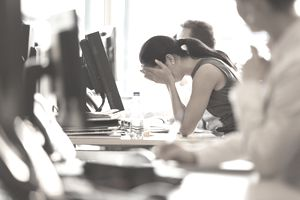 Stressed businesswoman with head in hands at office desk, considering a voluntary demotion.