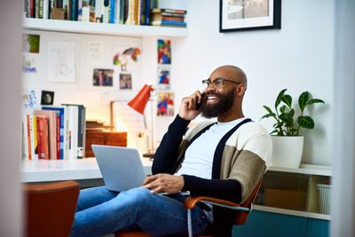Cheerful businessman working from home on phone