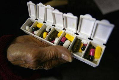 Close up on a woman's hand holding a pill organizer, representing health savings accounts.