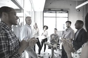 Smiling business people clapping in office meeting