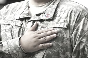 Man with hand over heart in military uniform.