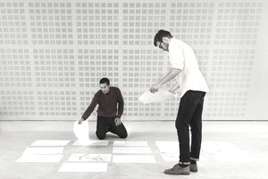 Project managers setting the flow of a project by laying out information pages on the floor of an office.