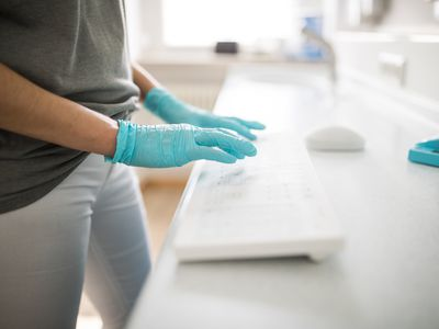 Woman in medical gloves working on computer