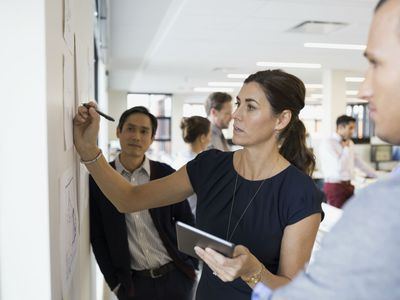 Businesswoman outlining a new product plan at white board while two coworkers look on