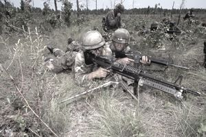Military personnel firing machine guns