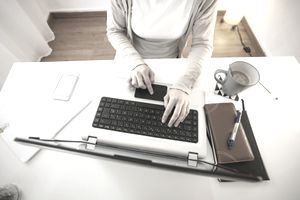Woman working at modern home office, partial view