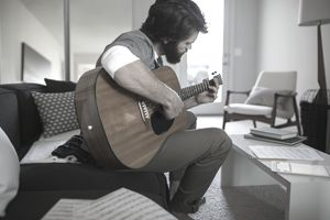 Man playing guitar writing music in living room