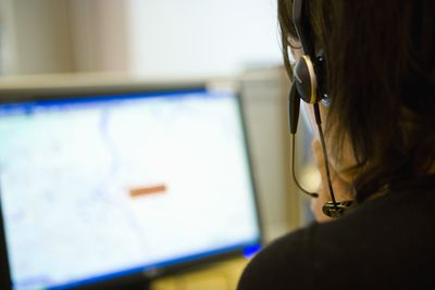 Emergency services dispatcher wearing a headset in front of a computer.