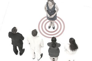 Businesswoman standing on bull's-eye with people in a row