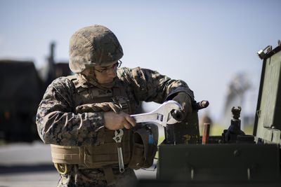 Marine combat engineer working with tools in the field wearing a flack jacket and helmet.