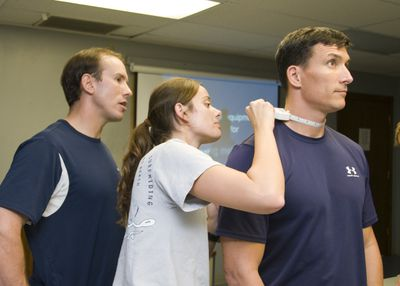 Mark McFarland, a fitness program coordinator for Navy Region Hawaii, observes Cryptologic Technician (Interpretive) 2nd Class Shannon Forbes as she performs a body composition assessment on Senior Chief Navy Diver Paul Adams as part of the Command Fitness Leader course.