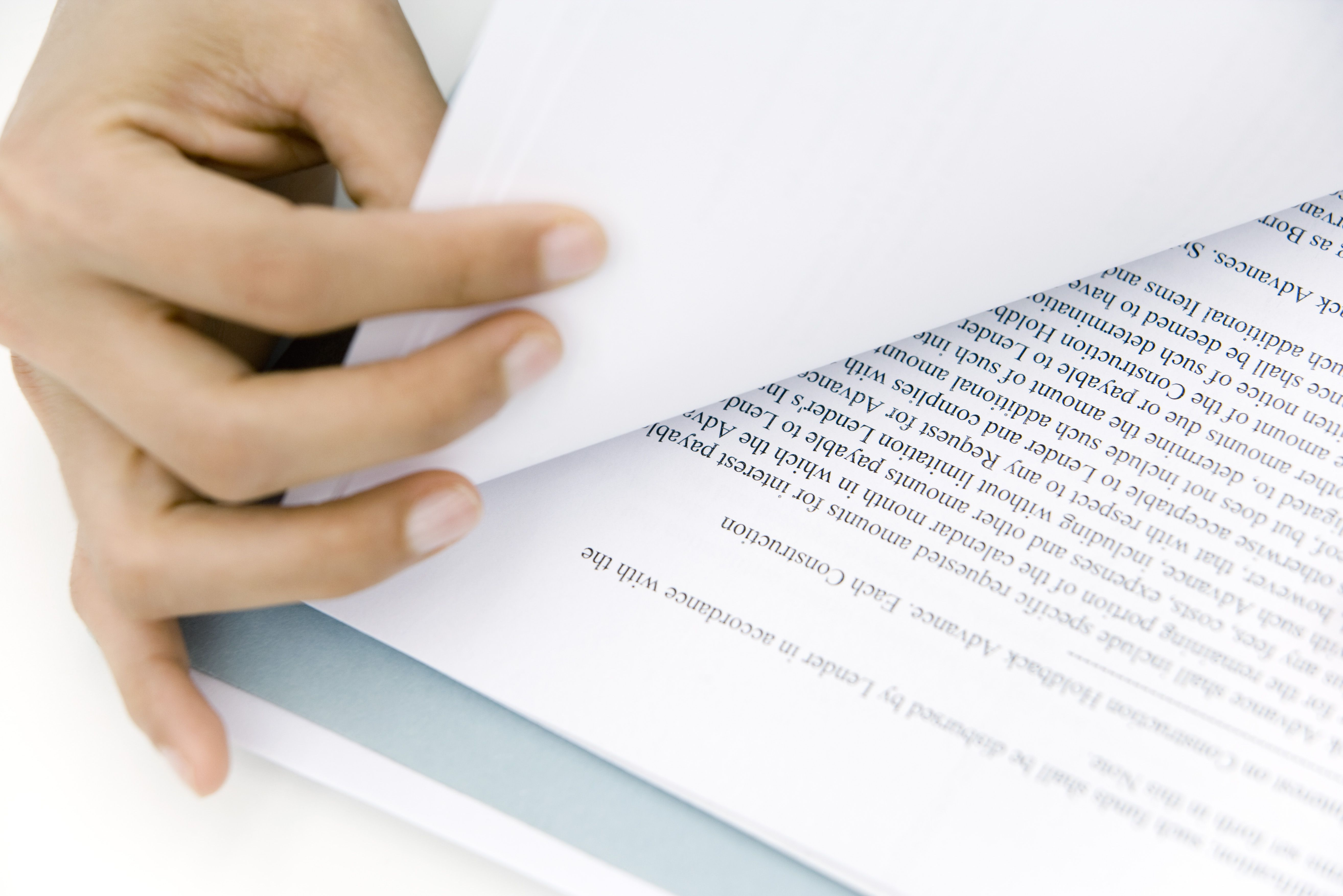 Hand turning document page, close-up