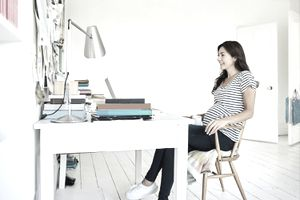 A pregnant woman sitting in a home office