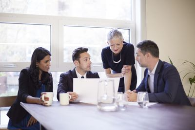 Mature business woman in a meeting with employees.