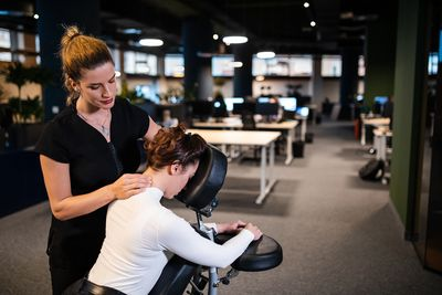 Exhausted young business woman enjoying neck massage after long hard working office day