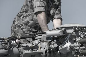 An Army armament/electrical/avionic systems repairer working on parts of a helicopter's rotor.