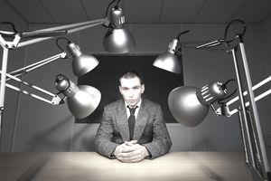 Businessman being interrogated at desk with several bright lights shining on him