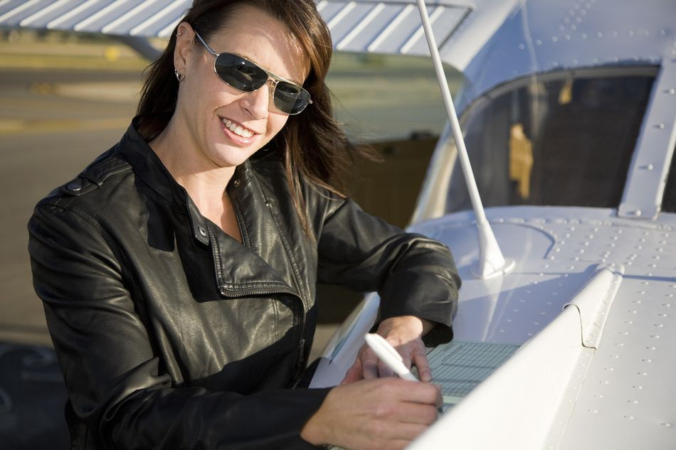 Woman Pilot Standing Next to an Airplane