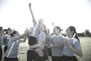 Exuberant high school girl soccer team celebrating and cheering on field