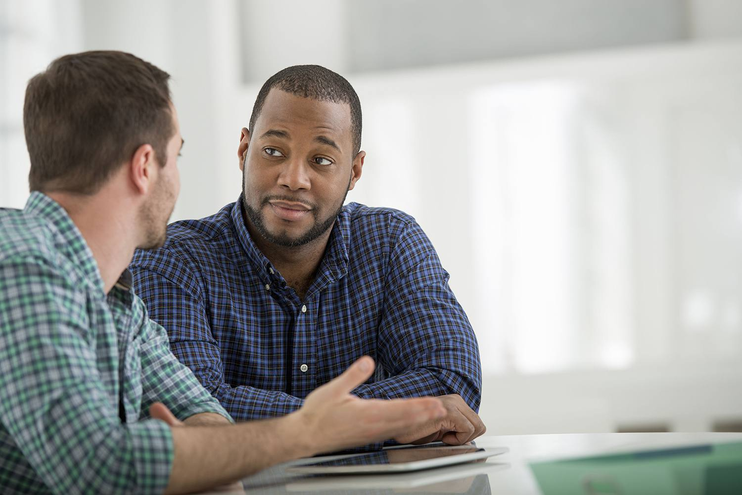 Man listening attentively to another man talking