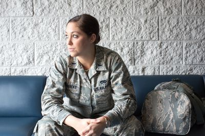 Air Force soldier sitting on a bench at an airport.