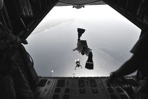 A U.S. Air Force pararescueman jumping out of an HC-130P Hercules aircraft.