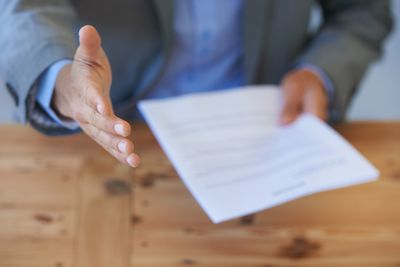 Application holding a resume reaching out for a handshake.