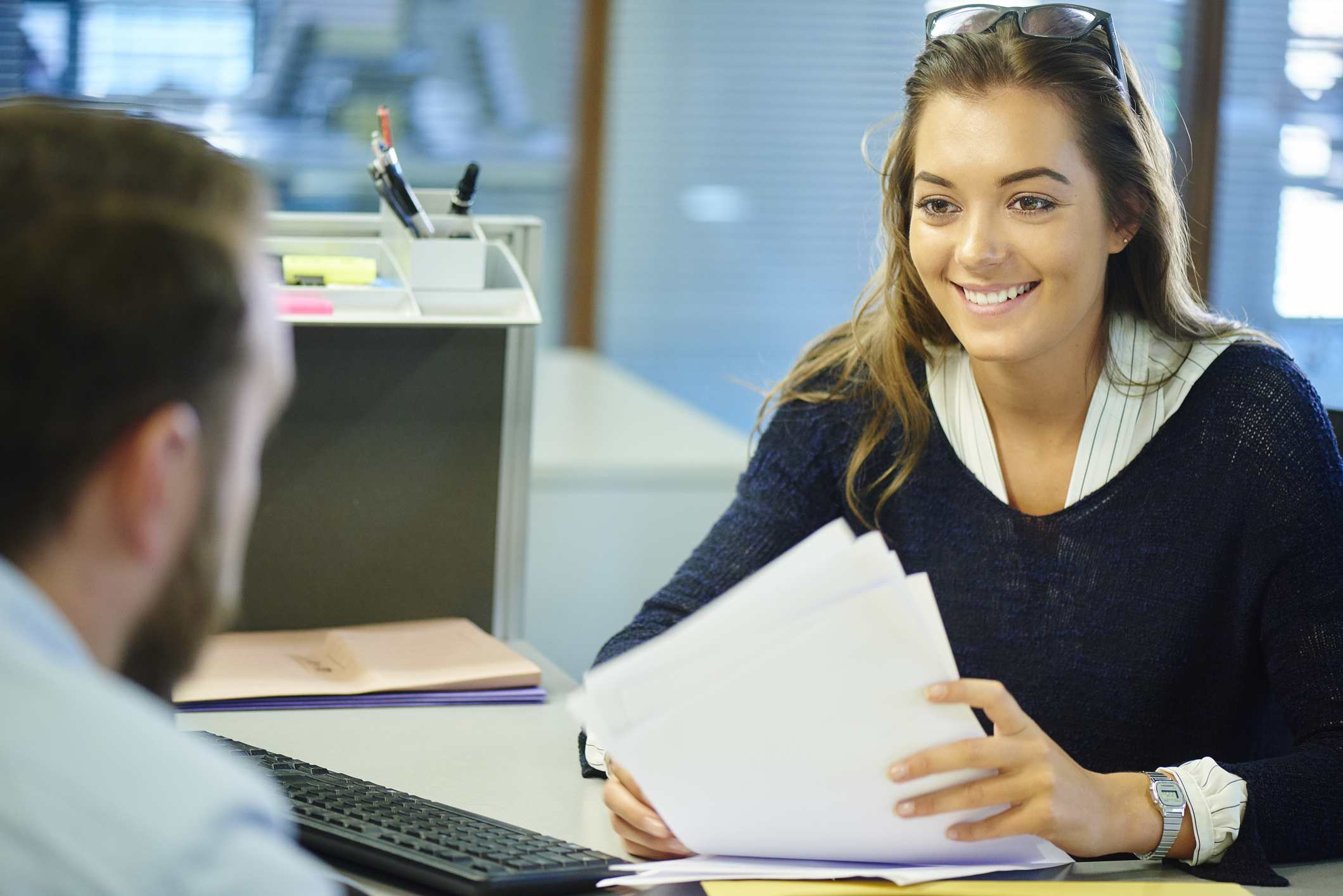 Young woman holding papers, speaking with employer