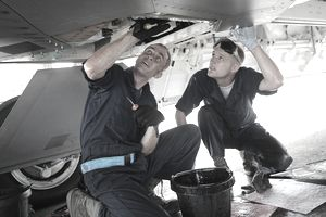 U.S. Air Force Staff Sgt. Jeremiah Smith (left) and Senior Airman Theodore Cupp, both crew chiefs with the 525th Expeditionary Aircraft Maintenance Unit, do maintenance work on the system one hydraulic pump underneath an F-22 Raptor aircraft at Andersen Air Force Base, Guam, on June 2, 2009. The airmen are deployed from Elmendorf Air Force Base, Alaska.
