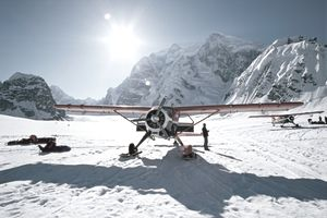 Small plane on ice and snow in front of snowy mountains under a brilliant sun.