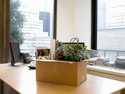 Box of personal items on office desk that hopefully includes employer severance pay