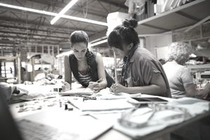 Women sketching at workbench in workshop