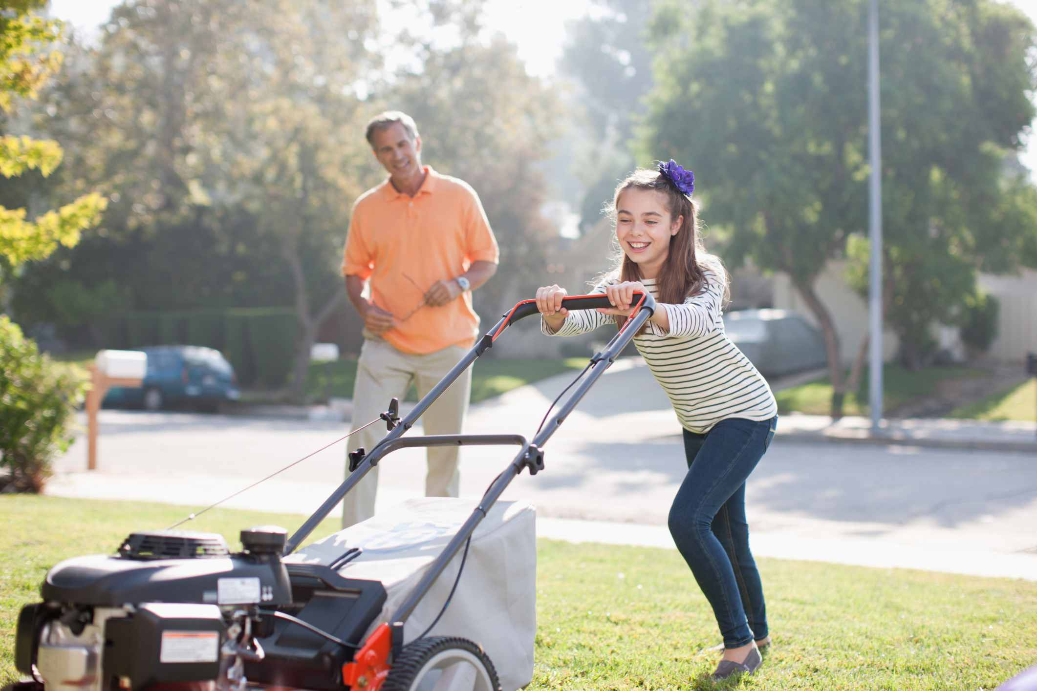 Girl mowing lawn with dad overlooking