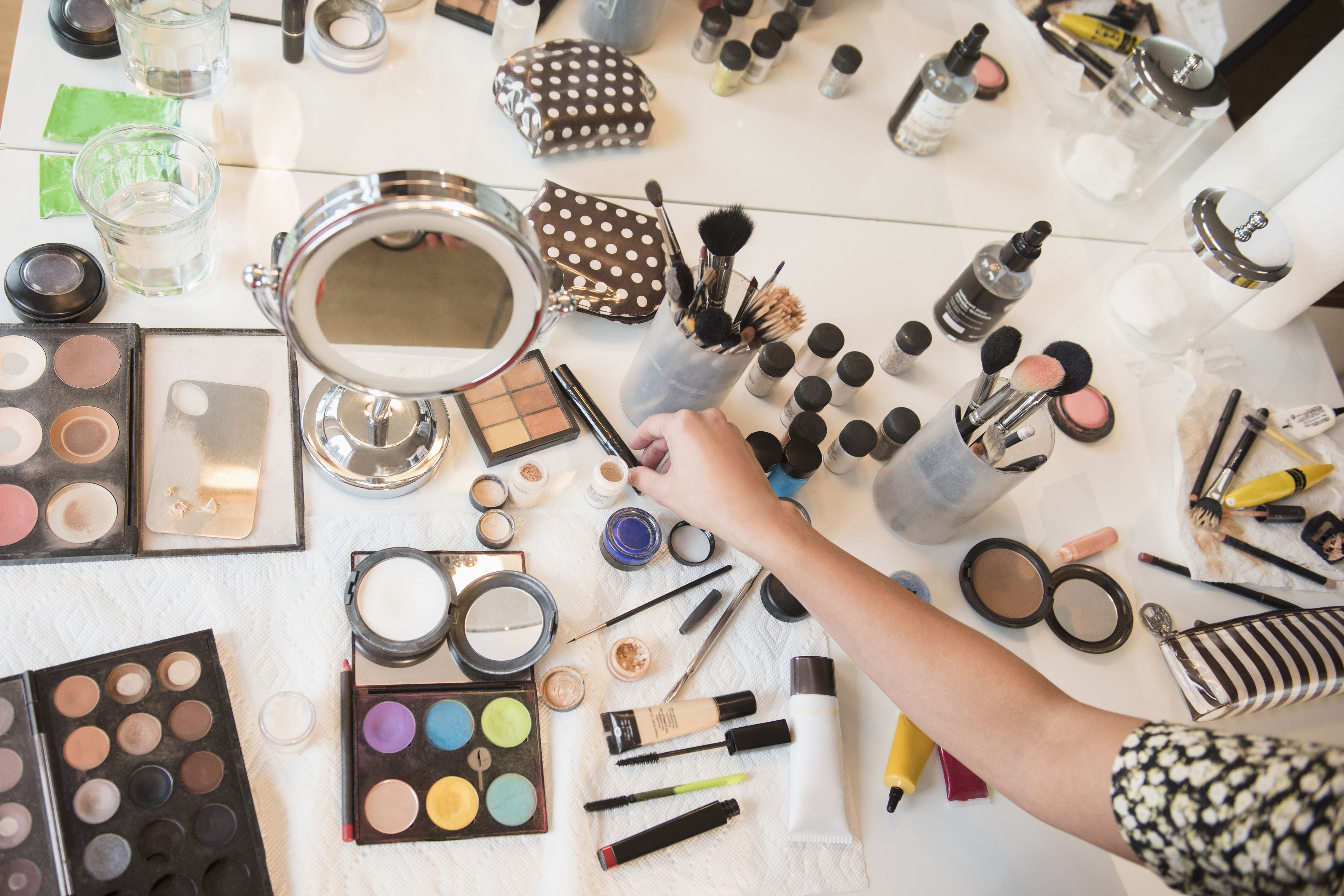 Woman selecting makeup from table